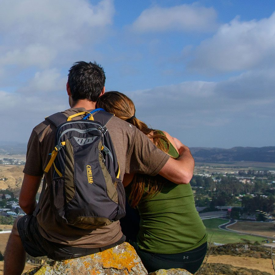 Two people looking out over a hill while hiking