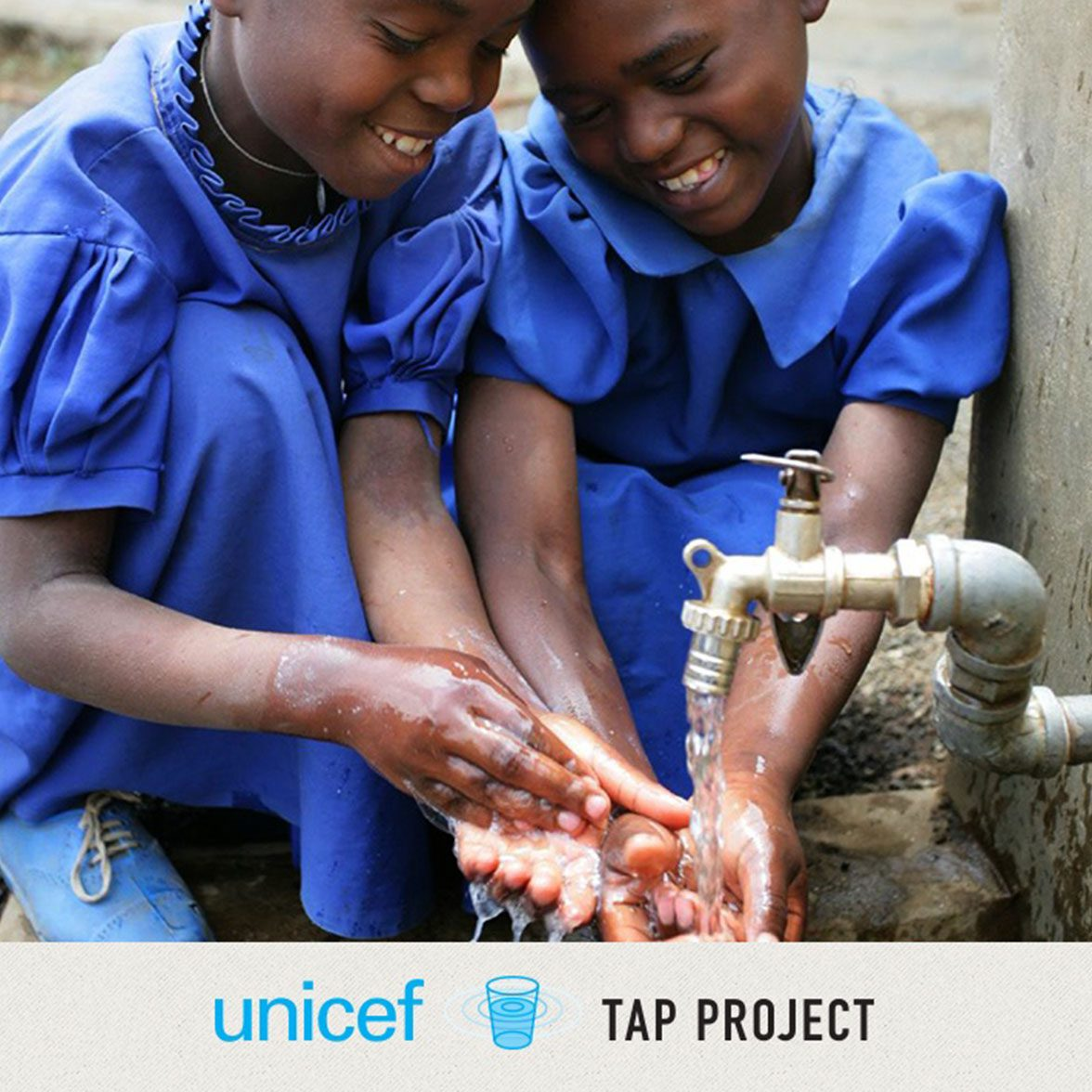 Two young girls washing their hands
