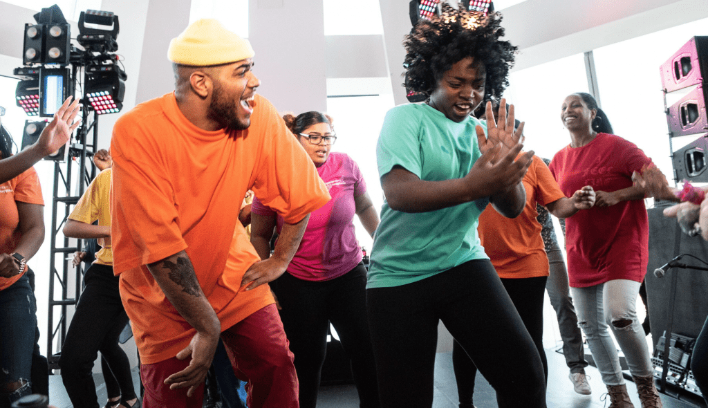 A group of young african american students in brightly colored t-shirts dancing at an LG Experience Happiness event