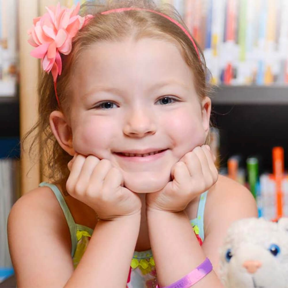 a young girl resting her face on her hands smiling at the camera